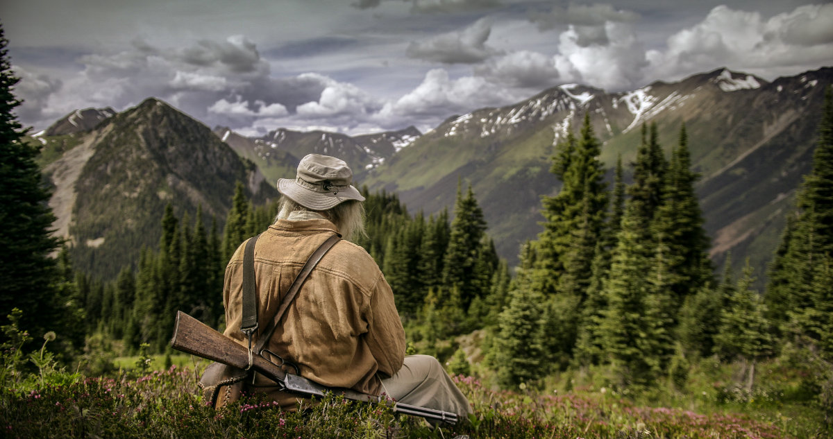 Old man sitting with his gun over his back looking at a mountain view.